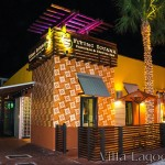 "The exterior facade of the Flying Iguana in Neptune Beach at night. An iconic corner has been created by covering about 11 feet of each adjoining wall from knee-height to rooftop with the 10"" Tradewinds pattern decorative cement tile."