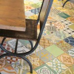 A close-up of the Flying Iguana dining room, focused on a table and chairs, with a good view of the floor. The floor is covered with a select mix of patchwork cement tile from Villa Lagoon Tile.