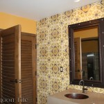 A photo of the ladies' restroom of the Flying Iguana, focusing on the wall with a vanity and mirror. The wall is clad with Torino pattern decorative cement tile from Villa Lagoon Tile.