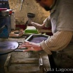 Cement tile production. The Artisan is clamping the custom hexagonal shape mold to the mold's base.