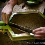 Cement tile production. The artisan levels the cement in the mold with a straight edge.