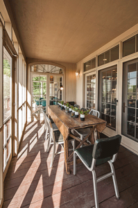 Long dining table in a screen porch connected to the family room
