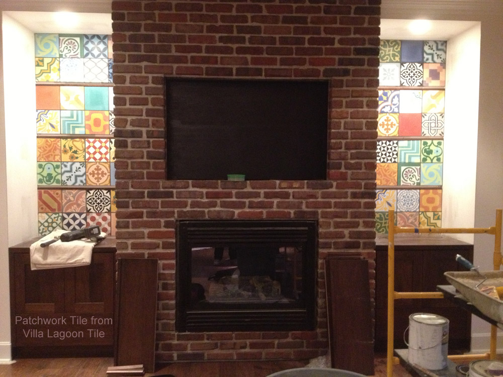 Encaustic cement tile in the back of custom shelves on either side of a brick fireplace.