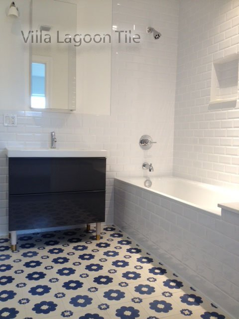 "A white bathroom, accented by ""Ambrose"" blue-and-white cement tile by Villa Lagoon Tile."