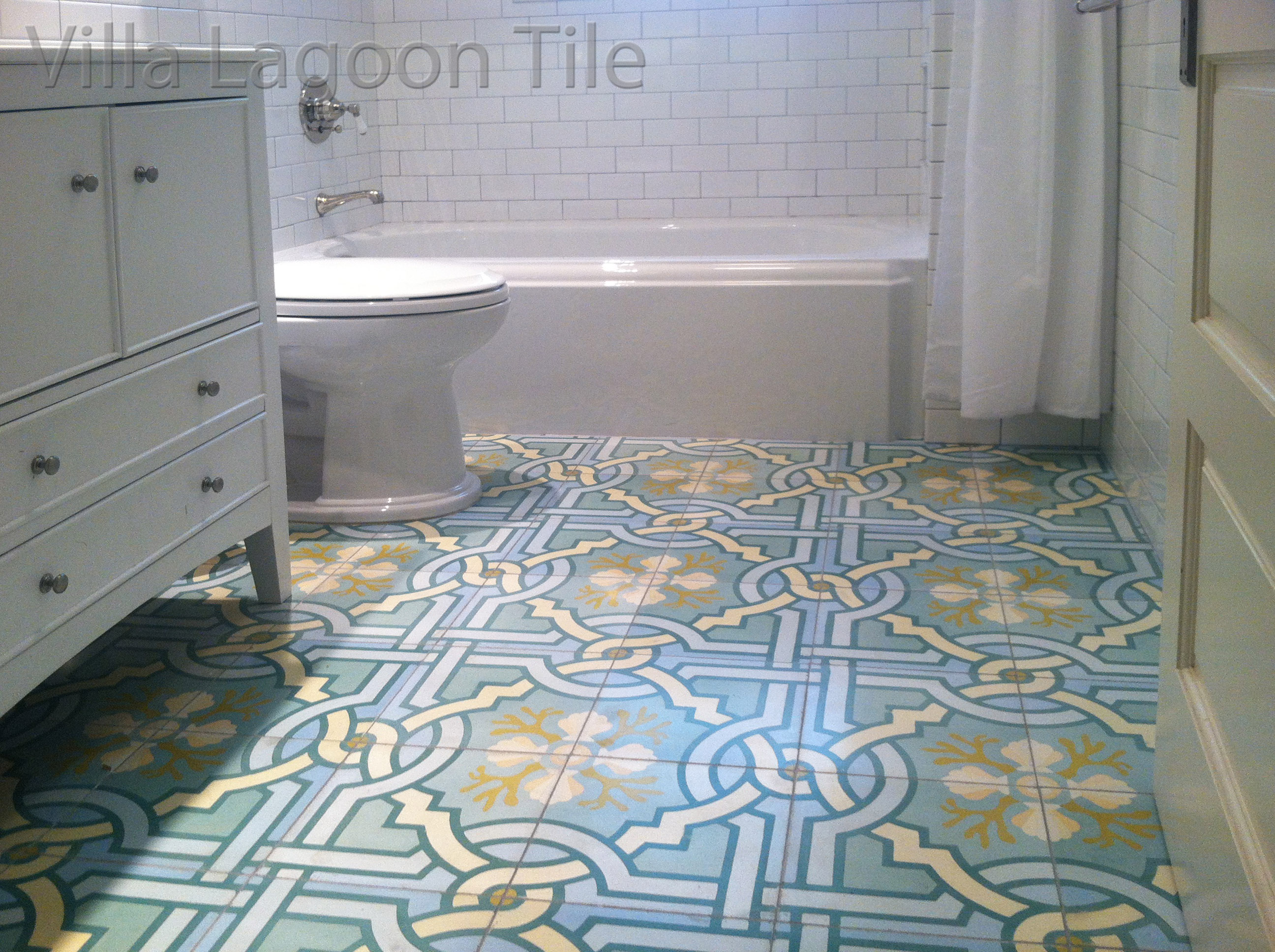 "Villa Lagoon Tile's original ""Venetian Azul"" cement tile brings a white bathroom to life."