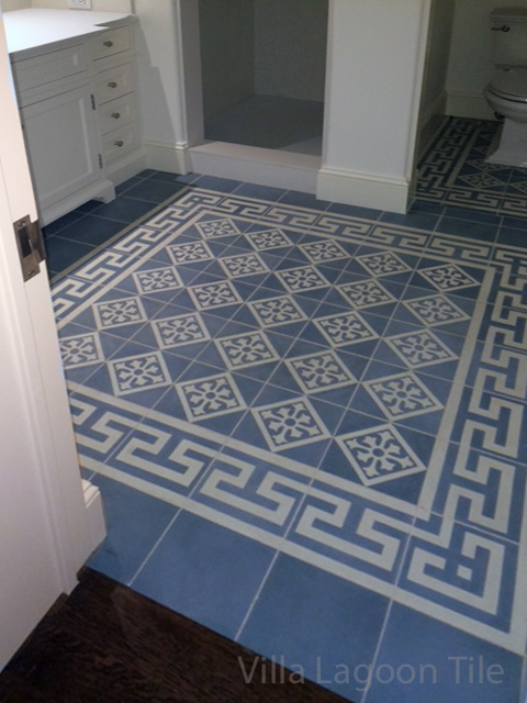 Beautiful blue and gray cement tile from Villa Lagoon Tile accents this white bathroom.
