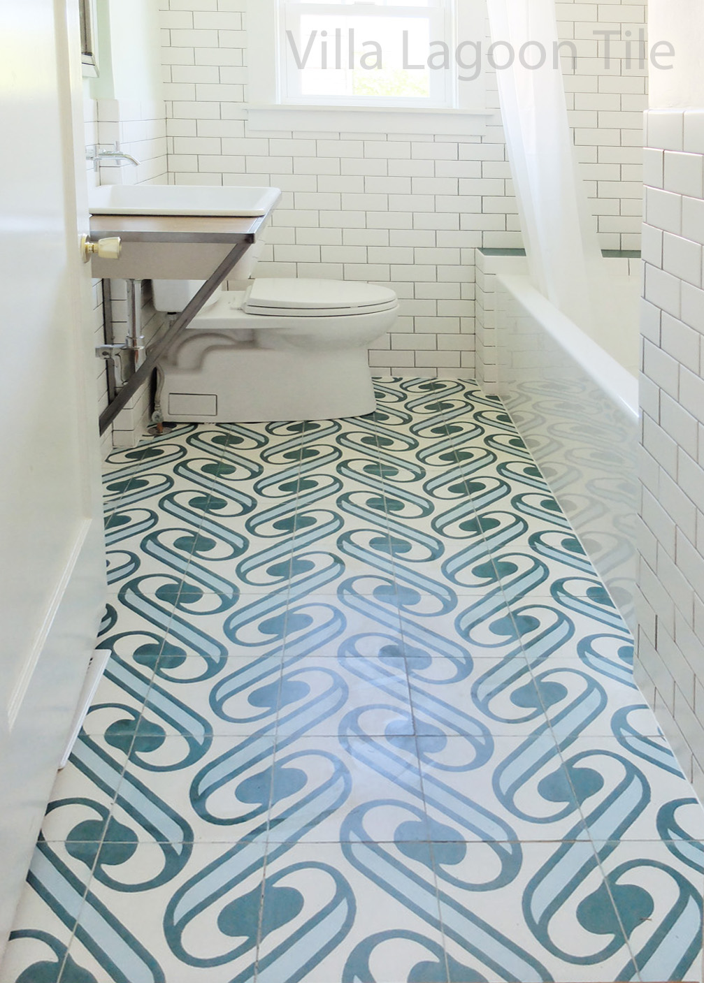 "Villa Lagoon Tile's exclusive ""Surf Agua"" cement tile, paired with subway tiles in a white bathroom."