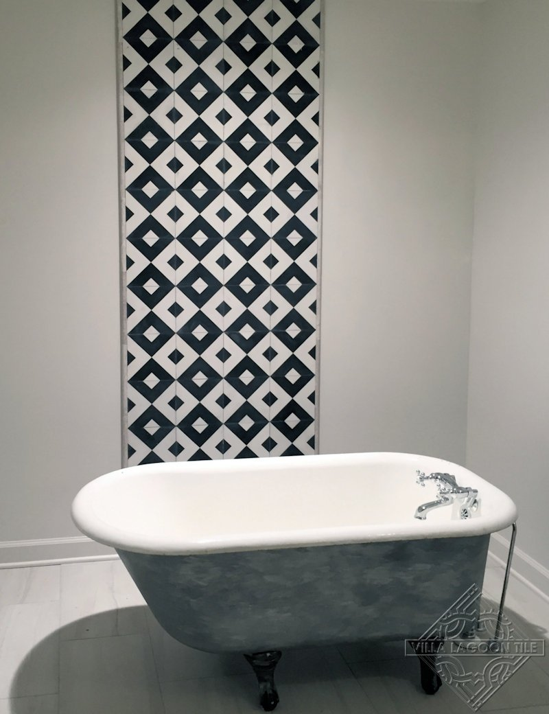 Black and white cement tile feature wall in bathroom.