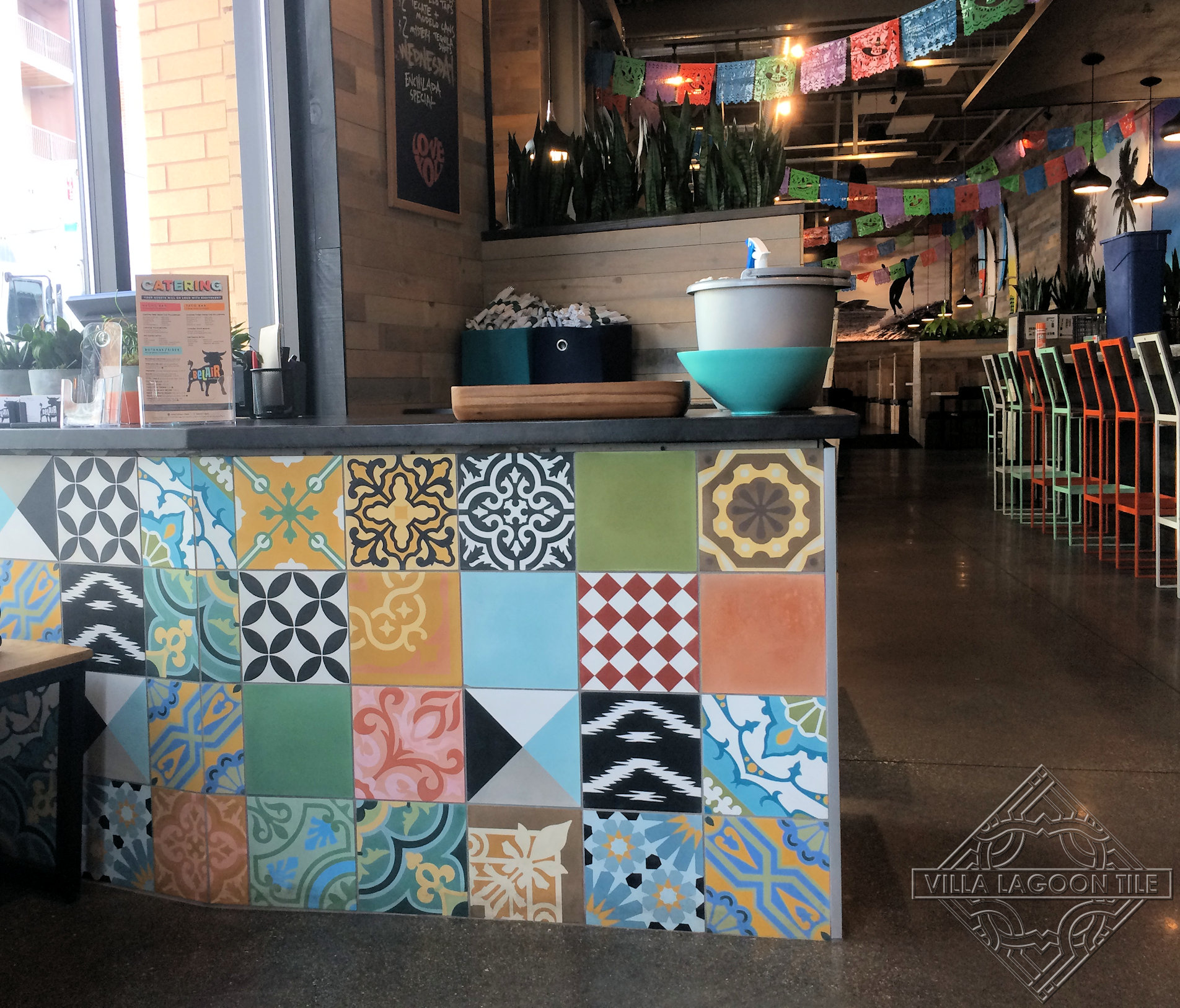 Colorful patchwork cement tile on the front of a Mexican restaurants hostess stand.