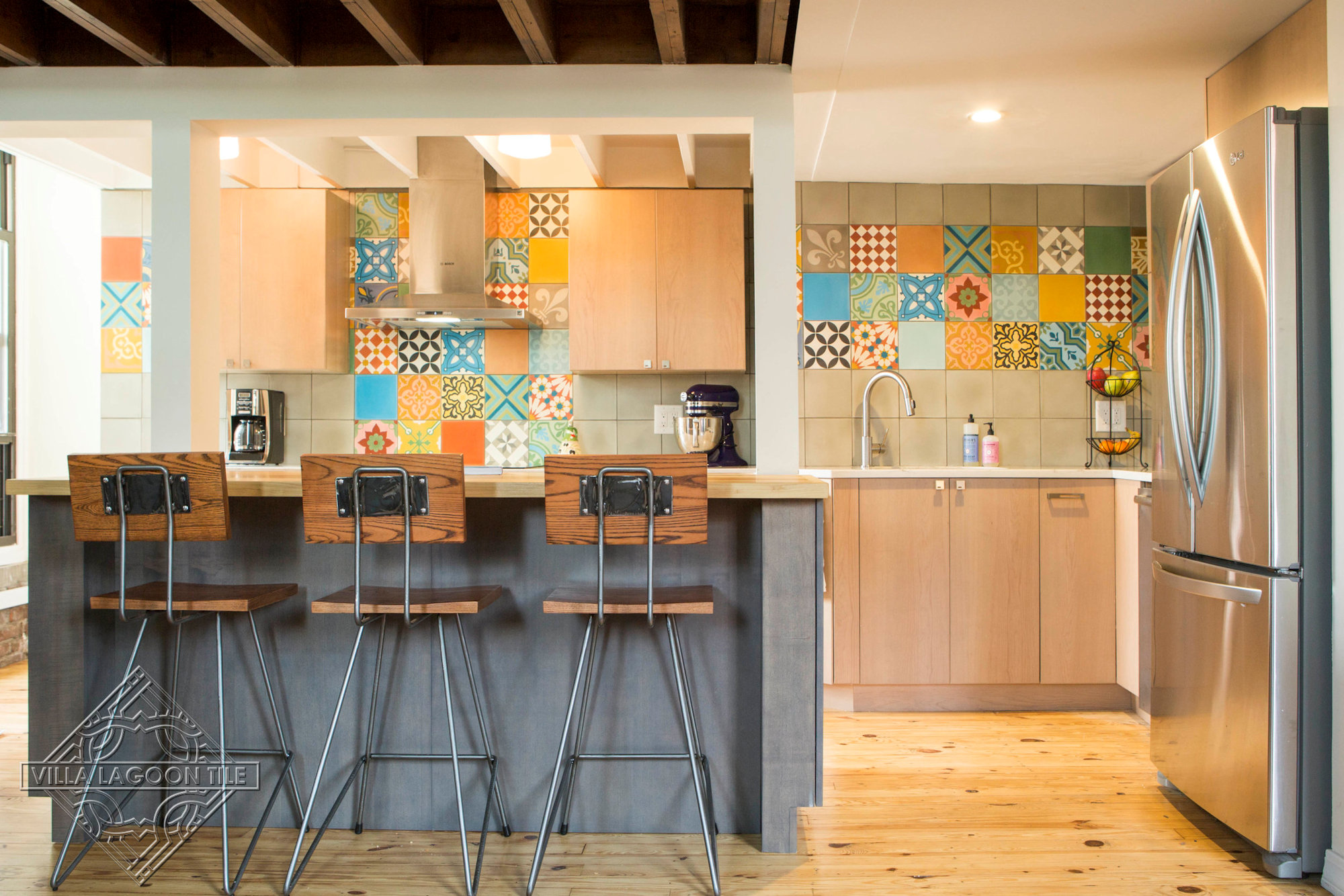 Small kitchen with colorful patchwork and solid cement tiles covering the wall.