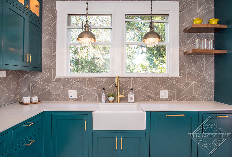 Teal kitchen with our Crow's Feet gray hexagonal shaped tile set on the walls.
