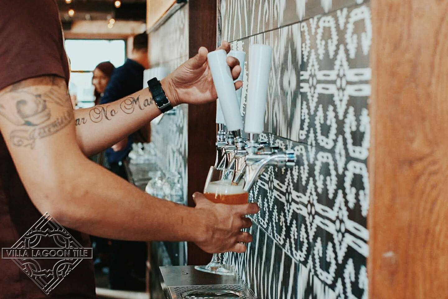 Decorative beer tap wall covered in our black and white Ikat Series cement tile.
