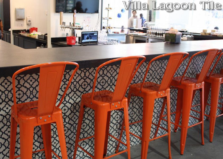 Counter front covered in our blue and white Breeze cement tile with bright Orange chairs in front.