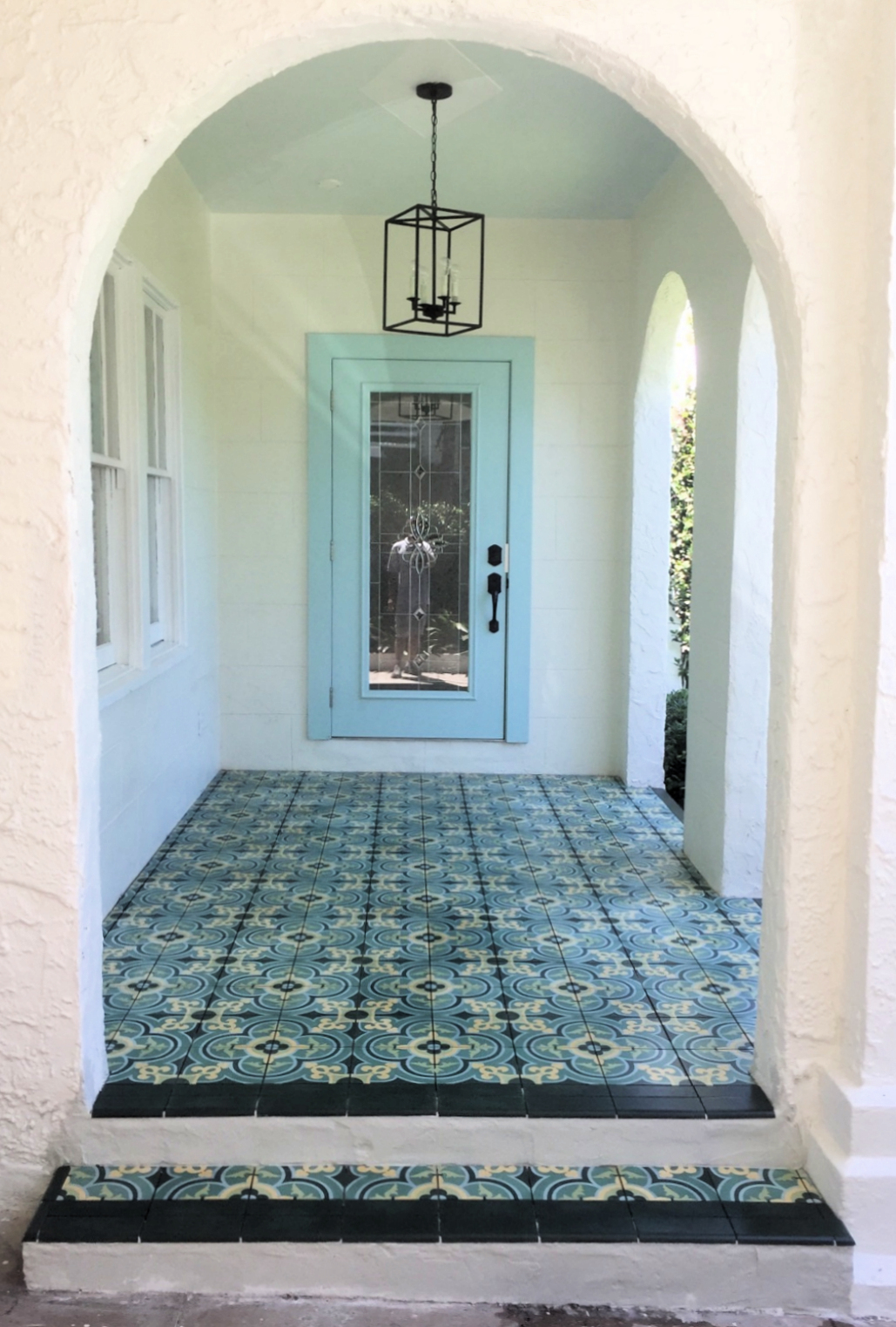 Entryway featuring green french inspired cement tile pattern bordered by solid dark green cement tile.