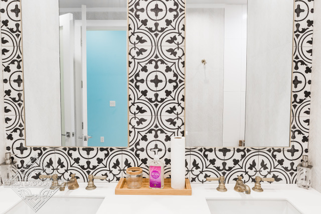 Traditional black and white quatrafoil cement tile pattern on a bathroom wall.